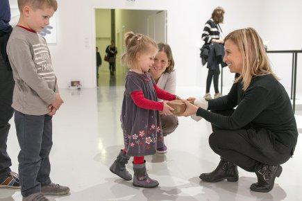 2 adultes présentent un objet à une enfant
